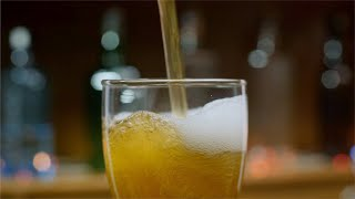 Bokeh shot of pouring fresh beer with foam into drink pint glass