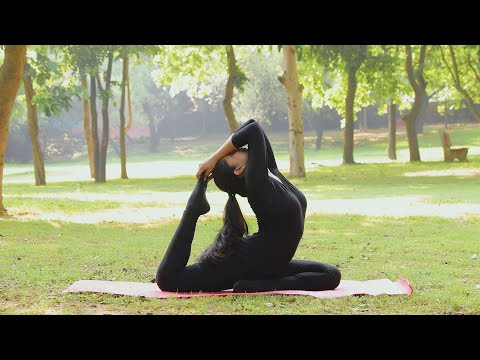 "a girl performing ""ardha kapotasana"" move in a park while"