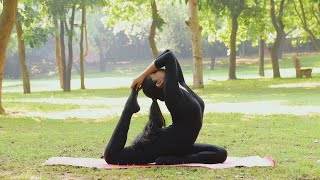 "A girl performing ""Ardha Kapotasana"" move in a park while exercising yoga"