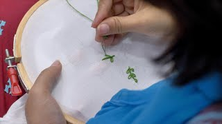 Embroidery - Shot of Indian woman / female stitching lazy daisy stitch in white cloth