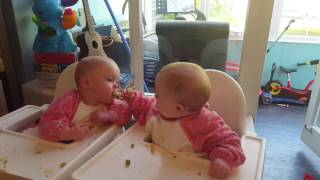 10 month old twins feeding each other.