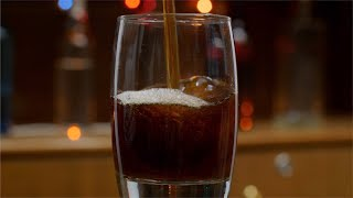 Shot of pouring cola / soda / soft drink into a glass at a restaurant