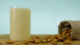 A small sack of almonds falling next to a transparent glass of almond milkshake
