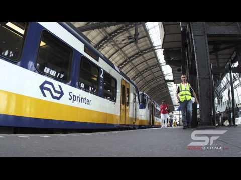 Time-lapse shot of train and people walking at a depot on 2013 in Amsterdam, Netherlands