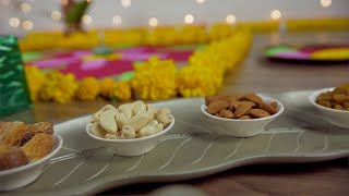 Pan shot of a designer plate of dry fruit bowls with colorful Diwali background - Indian festival