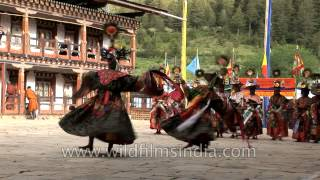 Monks wearing large black hats performs the Shana Cham dance in Bhutan