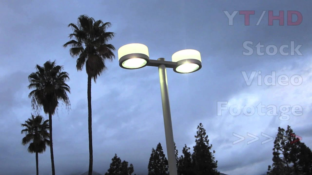 Parking lot lighting w two lights design on pole lit up against parking lot lighting w two lights design on pole lit up against gray skies hd stock video footage youtube aloadofball Image collections