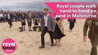 Prince Harry and Meghan walk hand in hand on Melbourne beach