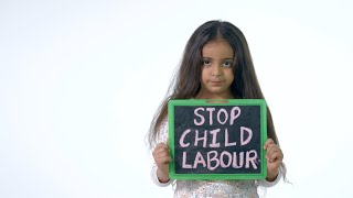 Young fearful girl showing slate with 'stop child labor' text - isolated over white background