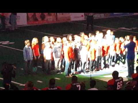 The 4th grade chior sings the national anthem at the Texas Revolution Arena Football game.