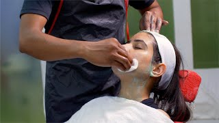 Slow motion shot of a beautician cleaning facial mask