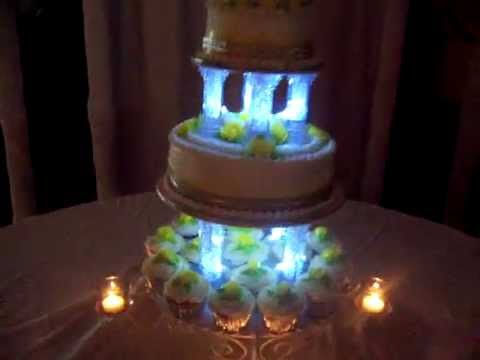 Wedding Cake With Room Dimmed Showing Lit Candles Cup Cakes And Pillars Up