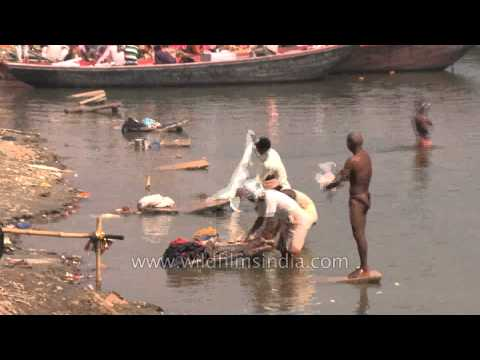 Heavily polluted Ganges river: Washing clothes and bathing in Varanasi
