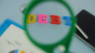 "Closeup shot of woman hands moving a magnifying glass over the word ""Debt"""