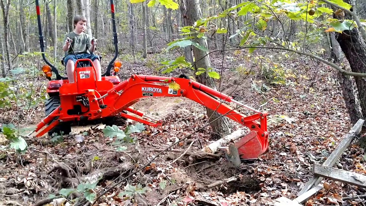 2013 Kubota BX25 backhoe removing stumps.