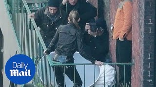 Catwoman! Gigi Hadid poses in black leather on a fire escape - Daily Mail