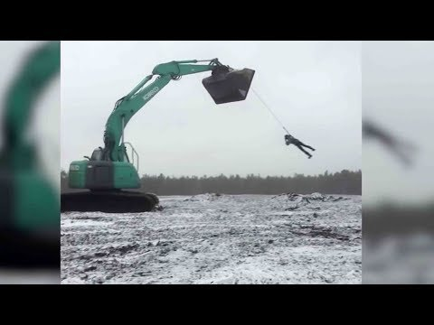 Download Youtube: Man performs crazy stunt harnessed to excavator