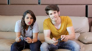Young couple sitting together on sofa playing video games