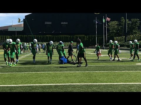 Oregon linebacker Jonah Moi breaks football dummy at Ducks' practice