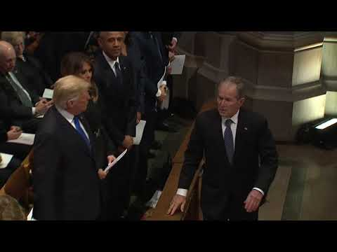 George W Bush sneaks candy to Michelle Obama at Bush funeral