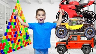 Малыш играет с гигантской пирамидой из стаканчиков катается на Мини байке и играет с машинками
