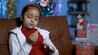 Pan shot of a young girl in Santa hairband sitting alone and eating potato fries on Christmas