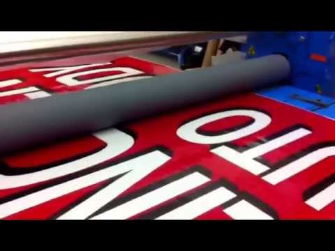 Mounting translucent film to sign face using laminator. Hollywood Graphics & Signs. Sacramento CA