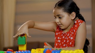 Charming cute Indian child girl playing at home with block colorful toys - childhood concept