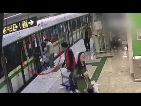 Man uses baby carriage to hold the train door