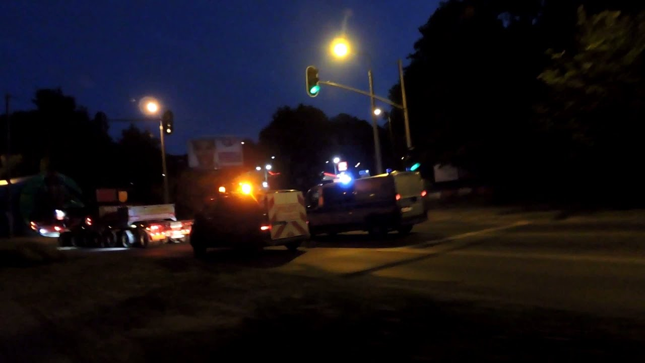 Radiowóz policyjny alarmowo na sygnale przebija się przez transport gabarytów