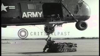 A US Army Sikorsky H-34 helicopter lifts off with a load of ammunition from an ai...HD Stock Footage