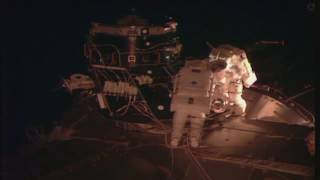 Space Station Crew Members Walk In Space to Connect Docking Adapter Component