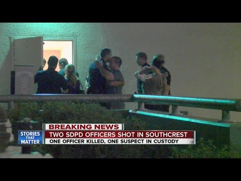 Officers console one another outside Scripps Mercy Hospital