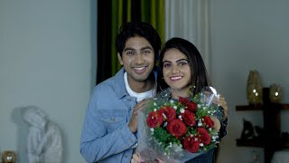 Cheerful Indian couple happily offering a bouquet of red roses to the camera