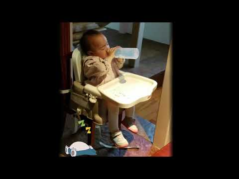 Toddler napping on a high chair while Drinking Milk.