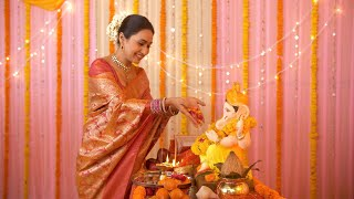 Beautiful young Indian woman offering flowers to Lord Ganesh idol on Ganesh Chaturthi
