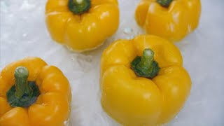 Slow motion shot of water droplets falling on the yellow bell peppers