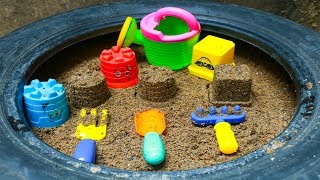 Play with Sand Molds and shovels toys on outdoor playground tire
