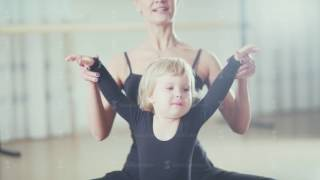 A teacher at the ballet school helps the little girl to do stretching