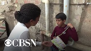 Venezuelan boy makes purse out of valueless money