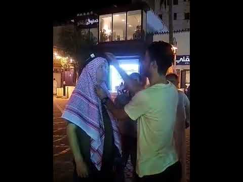 A stranger helps Jon with his Keffiyeh