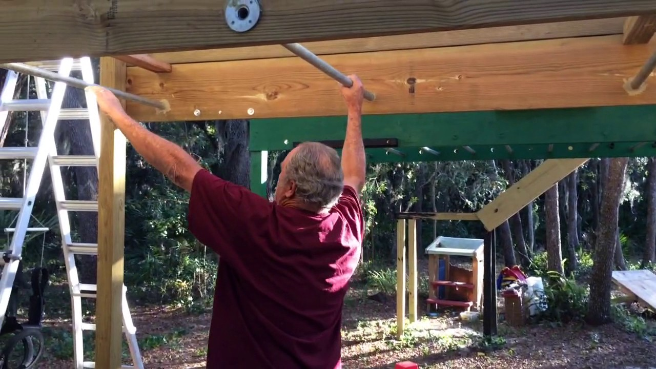 pa trying out the monkey bars on our backyard obstacle course anw