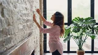 Pretty brunette house owner is decorating her loft style room hanging picture on brick wall choosing
