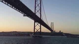 The Celebrity Eclipse cruise ship leaving Lisbon under the bridge