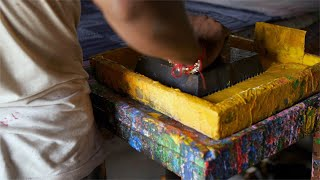 Block Printing - A worker dips the block into the trays of yellow colored dye
