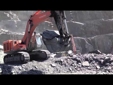 Hitachi ZX670 Excavator lifting a big Slate Rock...