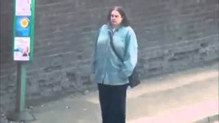 Lady listening to 'PTAF   Boss Ass Bitch' at bus stop