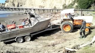 Rough dude at Tologa Bay pulling out stuck boat trailer with tractor