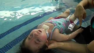 Kayli, with Trisomy 18, splashes the water during aquatic therapy, when prompted!