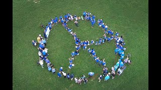 Human Peace symbol formed by kids roughly from 1 to 92